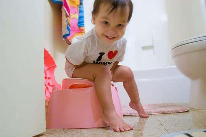 Asian toddler sitting on pink potty
