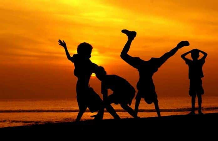 Children playing at sunset on beach