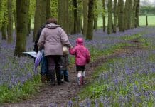 Family walking in blue flower forest with rainboots