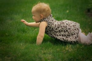 Nine month old toddler crawling in grass
