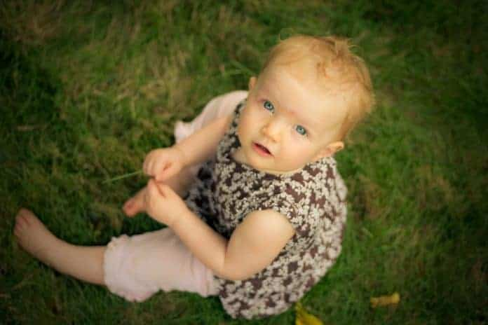 Nine month old Grace sitting on grass
