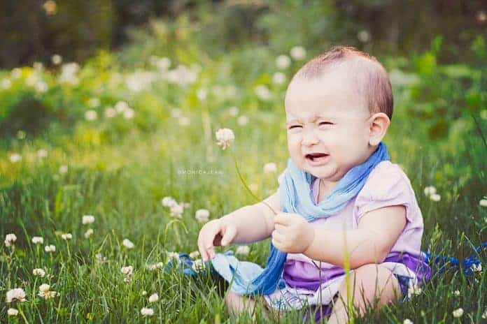 Infant crying on grass holding a flower