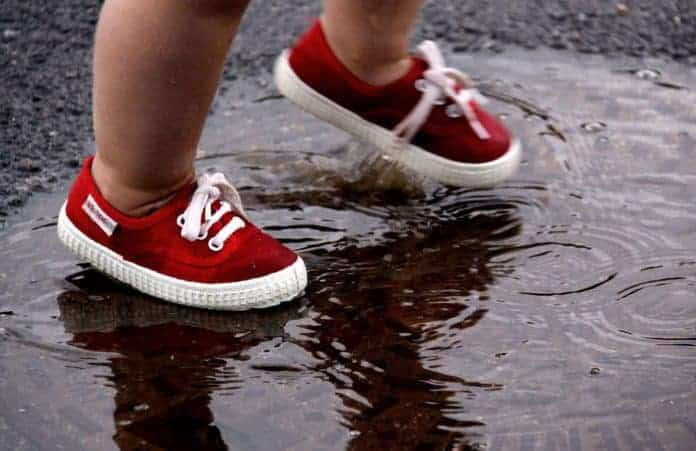 Toddler walking through puddle wearing little red shoes