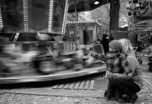Mother and toddler looking at merry go round spinning b&w