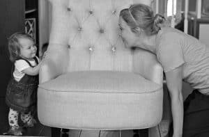 Nine month old infant playing peek a boo with mother behind chair