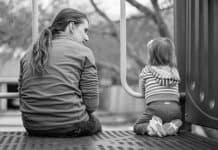 Black and white photo of Mother and toddler talking at playground