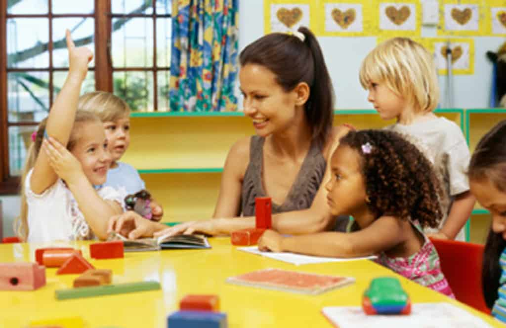 PreK teacher teaching at a table with children - Famlii