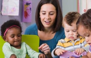 Preschool teacher working with african american toddler, little boy, and girl