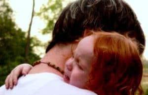 Sad crying redhead toddler hugging dad