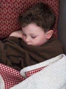 Sleeping sick toddler snuggled in blanket