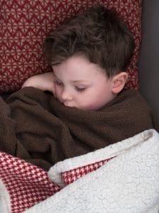 Sleeping sick toddler snuggled in blanket