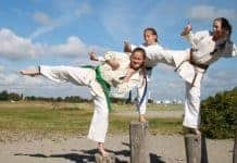 Three girls doing karate kicks on posts outside