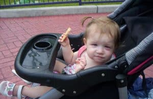 Toddler girl with pinkeye sitting in stroller