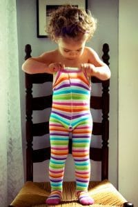 Two year old toddler putting on rainbow tights all by herself.