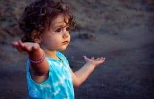 Two year old toddler at beach raising her hands in wonder