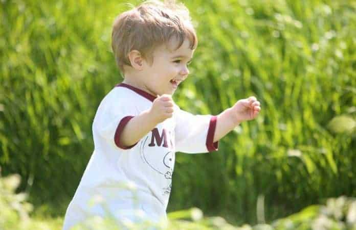 Toddler running through grass