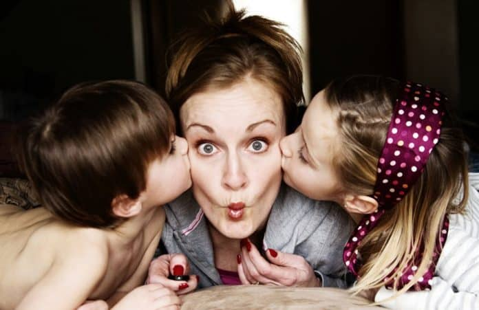 Mom with puckered lips being kissed by kids