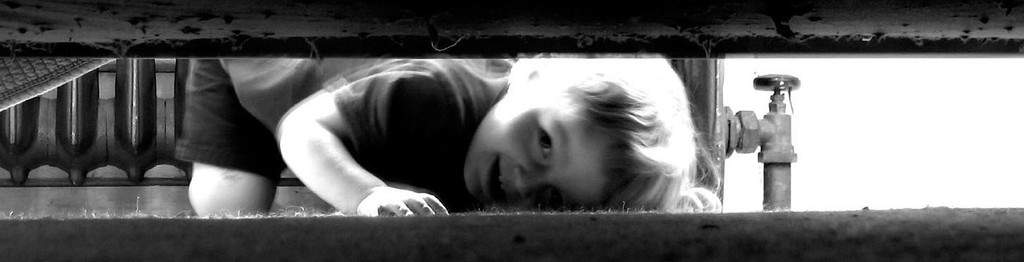 Toddler peeking under bed in B&W