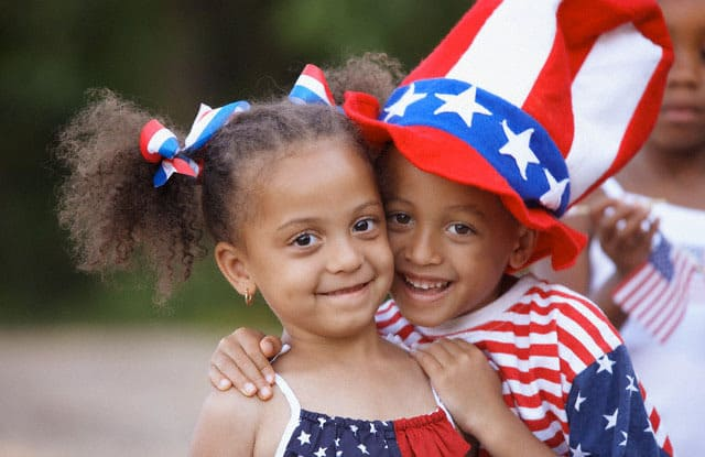 african american siblings hugging on fourth of july famlii