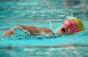 Girl swimming in pool at swim meet