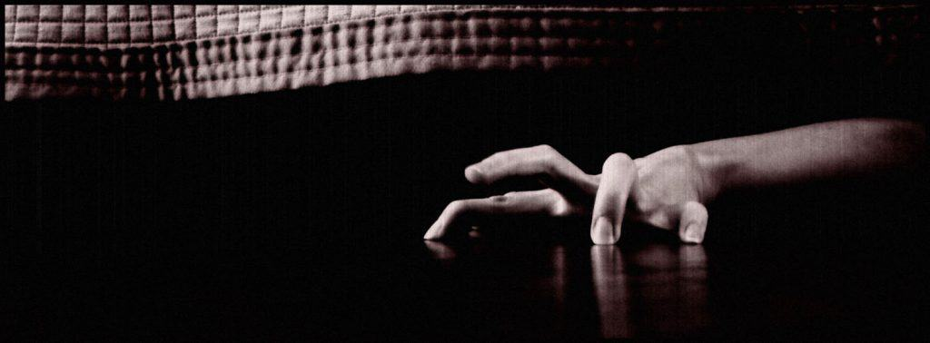 Black and White Photo of Hand sneaking out from under a bed