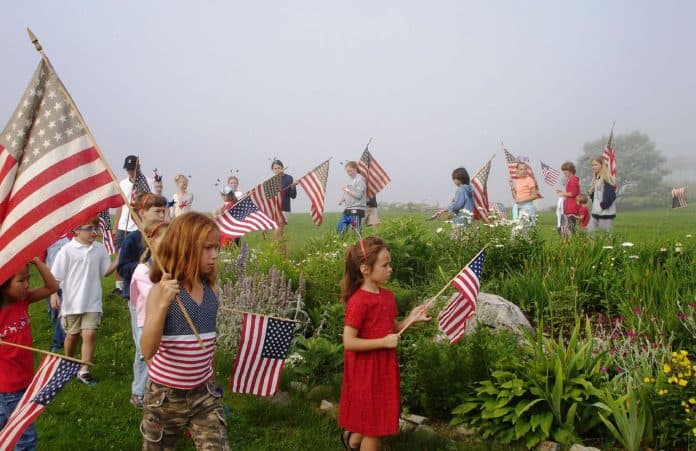 New Hampshire 4th of July Parade with Kids Carrying Flags through Grass