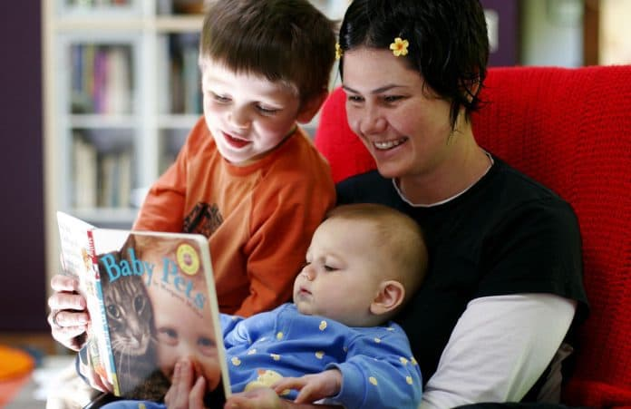 Mother reading to preschooler and infant