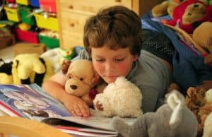 Preschooler reading on bed with stuffed animals