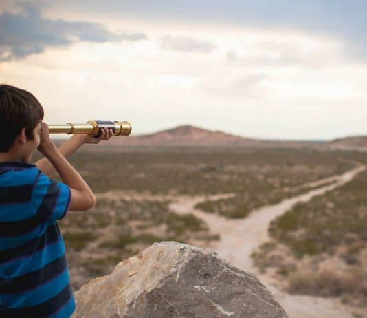 Boy looking through telescope in desert