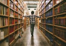 Boy walking through library of books
