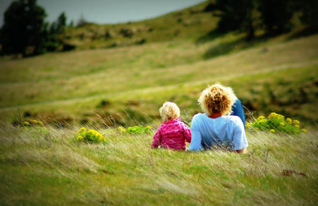 Dad and Daughter Relaxing on Hillside