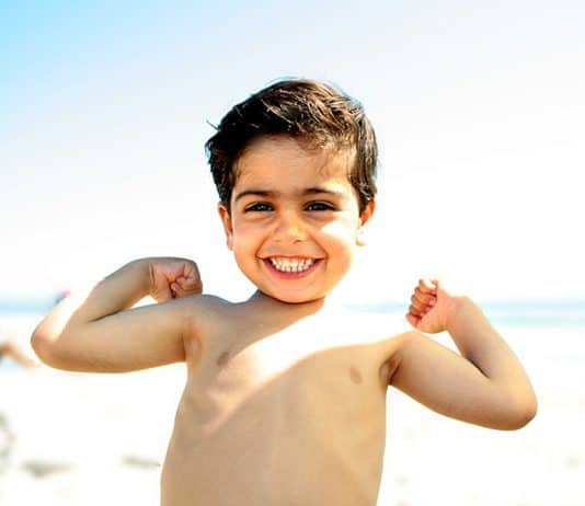 Little boy showing his muscles on the beach