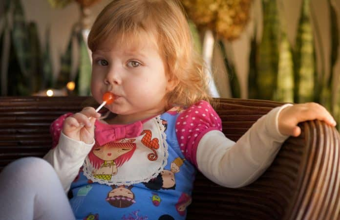 Toddler with lollipop looking skeptical