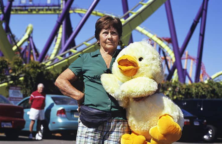 Grandmother holding stuffed duck at amusement park, not looking amused.