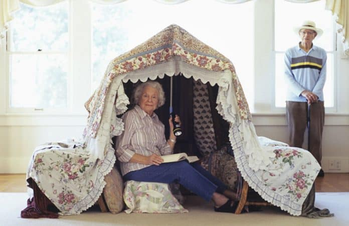 Grandmother in play tent reading with flashlight