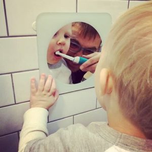 Father using electric toothbrush on toddler teeth