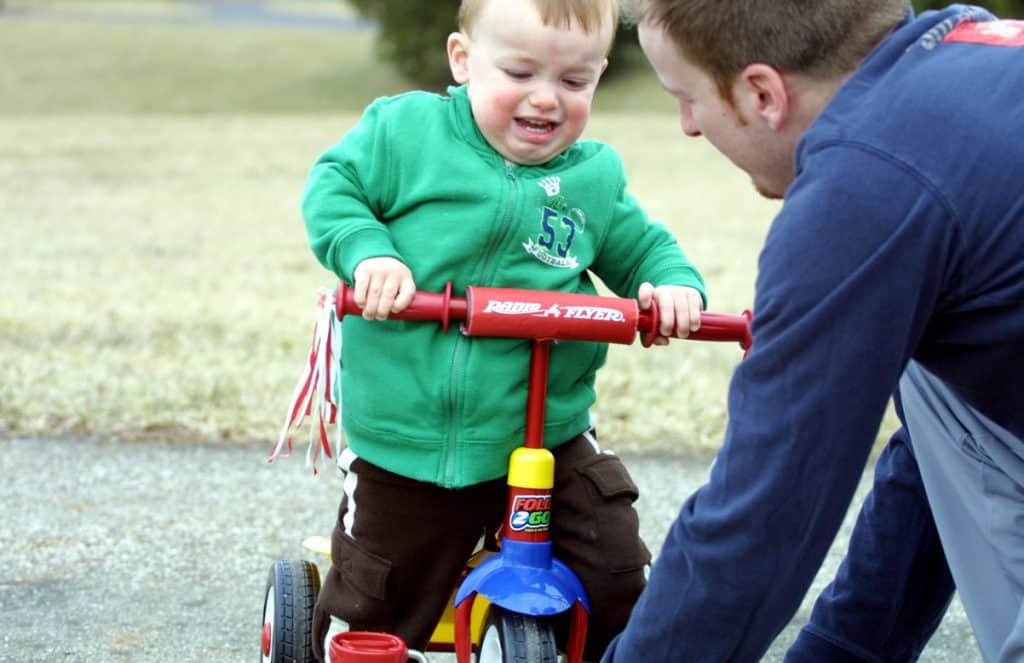 Toddler frustrated riding tricycle with patient father