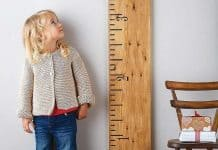 Girl looking up at growth chart measuring height.