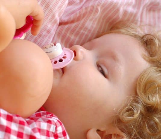 Sleepy toddler girl in bed with baby doll