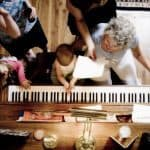 Baby, Grandmother, Sister, and Mom playing at the piano